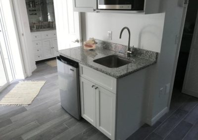 Placida wet bar_solid shaer cabinets_ plank tile floor_crown molding